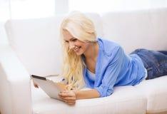 有片剂个人计算机计算机的微笑的妇女在家 库存照片