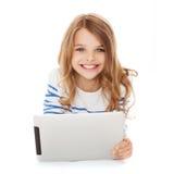 有片剂个人计算机计算机的微笑的学生女孩 免版税图库摄影