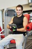 有片剂个人计算机计算机的微笑的年轻人在健身房 免版税图库摄影