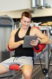 有片剂个人计算机计算机的微笑的年轻人在健身房 库存图片