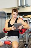 有片剂个人计算机计算机的年轻人在健身房 库存照片