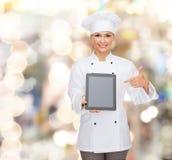有片剂个人计算机黑屏的微笑的女性厨师 免版税库存照片