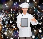 有片剂个人计算机黑屏的微笑的女性厨师 免版税库存图片