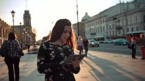 有片剂冲浪的互联网的年轻可爱的hansome redhair女孩在城市街道上 股票视频