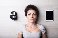 有片剂和一台数字照相机的妇女 免版税库存图片