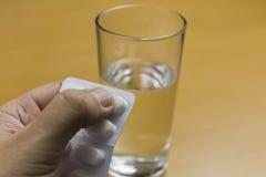 有片剂和一杯的手水 免版税库存图片