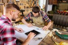 有片剂和图纸的木匠在车间 免版税库存图片