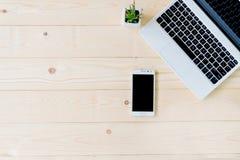 有片剂和巧妙的电话的膝上型计算机在工作场所 免版税库存照片