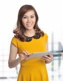有片剂和微笑的亚裔俏丽的妇女 免版税图库摄影