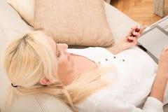 有片剂和樱桃的妇女在沙发 免版税库存图片