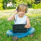 有片剂和耳机的男孩 免版税库存照片