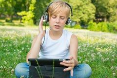 有片剂和耳机的男孩 免版税图库摄影