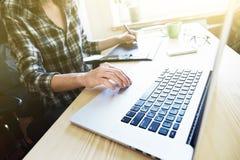 有片剂和膝上型计算机的设计师手 免版税库存照片