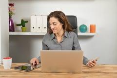 有片剂电话和膝上型计算机的多任务女实业家 库存照片