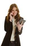 有片剂电话的美丽的女实业家 免版税库存图片