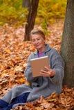 有片剂的一名妇女坐在一棵树下在秋天公园 免版税库存照片