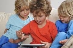 有片剂的三个男孩 库存照片