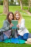 有片剂的两个女孩 库存图片