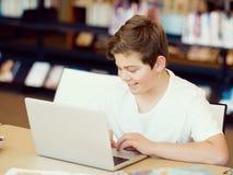 有片剂的十几岁的男孩在图书馆里 免版税库存图片