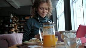 有片剂的可爱的年轻女人在咖啡馆,自由职业者概念 影视素材