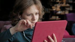有片剂的可爱的年轻女人在咖啡馆,自由职业者概念 股票录像