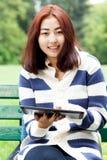 有片剂的女孩坐长凳 免版税库存图片