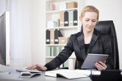 有片剂的女经理键入在台式计算机上的 图库摄影