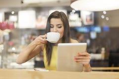 有片剂的妇女在咖啡馆 库存图片