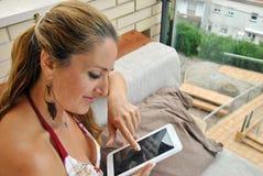有片剂的妇女坐沙发 库存图片