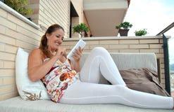 有片剂的妇女坐沙发 图库摄影
