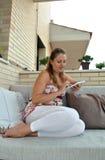 有片剂的妇女坐沙发 免版税库存照片