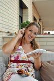 有片剂的妇女坐沙发 免版税图库摄影