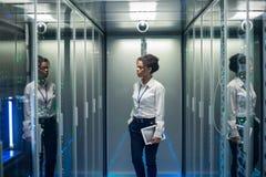 有片剂的妇女走通过服务器室的 库存照片