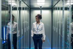 有片剂的妇女走通过服务器室的 免版税库存照片