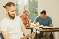 有片剂的学生男孩在她的同学前面 免版税库存图片