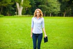 有片剂的小姐在公园 免版税图库摄影