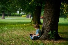 有片剂的小男孩在膝部坐在巨大的树下 图库摄影