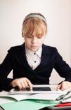 有片剂的小白肤金发的女孩在学校 免版税库存图片
