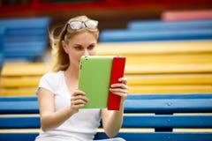 有片剂的少妇在手上,当坐长凳时 免版税库存照片