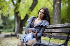 有片剂的少妇在长凳 免版税库存图片