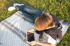 有片剂的年轻人在公园坐地毯绿草 免版税库存图片
