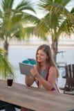 有片剂的年轻女人在海滩 免版税库存照片