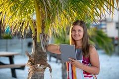 有片剂的年轻女人在海滩 免版税库存图片