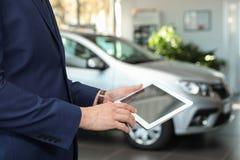 有片剂的年轻汽车推销员在经销权中, 免版税库存照片