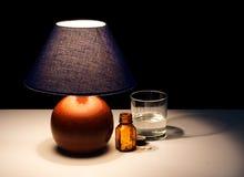 有片剂的床头柜灯,可能水的失眠 图库摄影