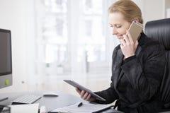 有片剂的愉快的女实业家谈话在电话 库存照片