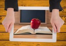 有片剂的手在显示书用红色苹果的黄色桌上 免版税库存照片