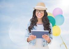 有片剂的时髦妇女反对晴朗的天空和气球有火光的 免版税库存图片