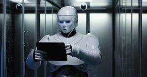 有片剂的未来派机器人在服务器屋子里 库存图片