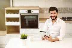 有片剂的男孩在厨房里 免版税图库摄影